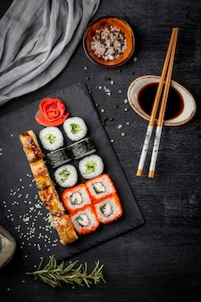 Japanese rolls, soy sauce and sticks on black slate board and black background top view