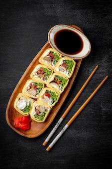 일본 검은 배경에 닭고기와 크림 치즈 롤. 고품질 사진