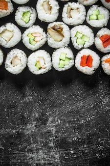야채, 연어, 닭고기를 곁들인 일본식 롤. 소박한 테이블에