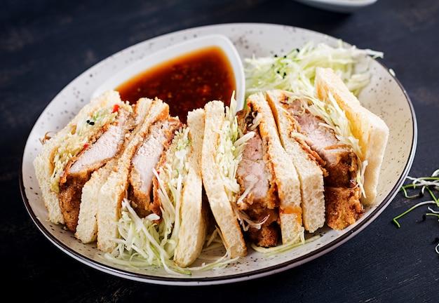 Японский бутерброд с панированной свиной отбивной, капустой и соусом тонкацу.