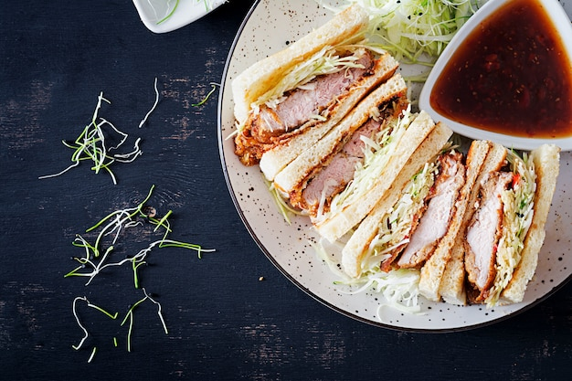 Japanese sandwich with breaded pork chop, cabbage and tonkatsu sauce