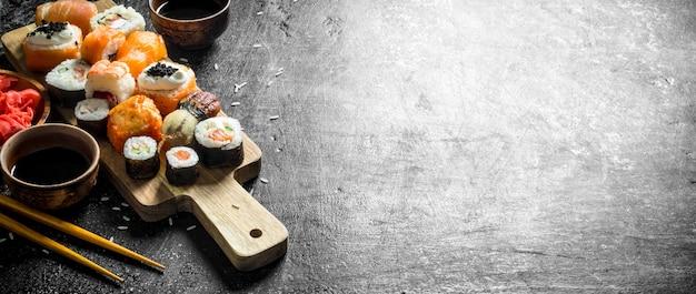 Японские суши из морепродуктов на разделочной доске. на темном деревенском фоне