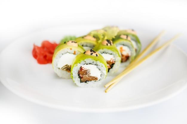 생강과 와사비가 들어간 흰 접시에 일본 해산물 스시, 롤과 젓가락