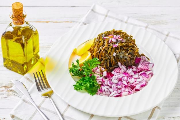 Японский гарнир: салат вакаме из морских водорослей, маринованных в лимоне, нарезанный кубиками красный лук и дольки лимона, на белой тарелке с петрушкой, посыпанной кунжутом, хлопьями чили сверху, вид сверху, крупный план
