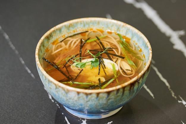 검은 돌 테이블에 파란색 세라믹 그릇에 계란과 돼지 고기가 들어간 일본 스프라면