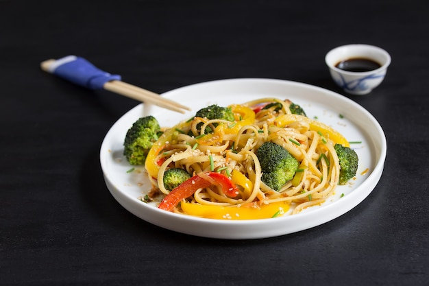 Japanese stir fry udon noodles with vegetables on the black table, cooked in wok