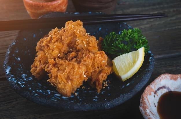 Хрустящий жареный цыпленок по-японски при слабом освещении в помещении.