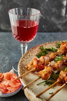 赤ワインと生姜のグラスと木の板に和風焼き鳥シャシリク