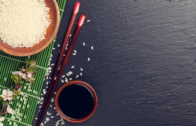 黒い石の背景に日本の寿司箸、醤油丼、ご飯と桜の花。コピースペースのある上面図。トーン
