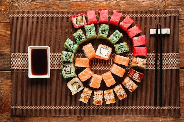 Японские суши, искусство еды. большой набор свежих булочек в виде разноцветной спирали на коричневой соломенной циновке, плоская укладка. фото меню роскошного ресторана, традиционная восточная кухня.