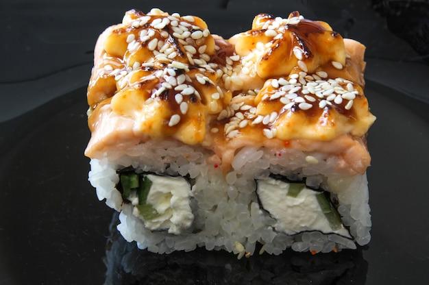 검은 배경에 일본 스시 음식 참치 연어 새우 게 아보카도와 함께 구운 따뜻한 롤
