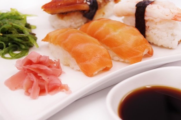 白いお皿に生姜と海苔のサラダを添えた日本の寿司料理。