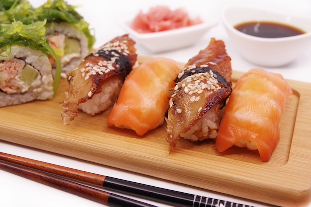 Japanese sushi food on a wooden tray, served with ginger, soy sauce and seaweed salad