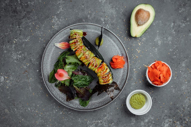 Японские суши - зеленый дракон. авокадо, лук, лосось и сыр суши. вид сверху.