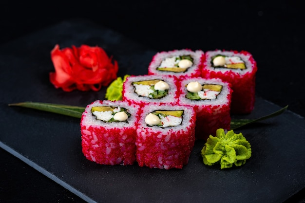 Japanese sushi in red flying fish roe tobiko caviar isolated on dark