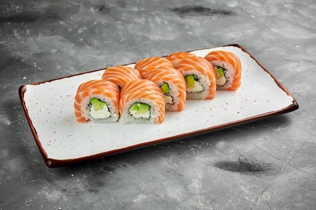 日本の巻き寿司-灰色のテーブルの白いプレートにサーモン、クリームチーズ、アボカドを添えたフィラデルフィア。日本料理。閉じる