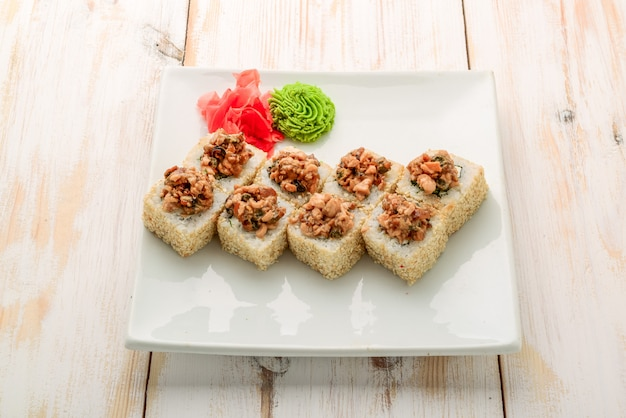 Japanese sushi roll topped with spicy salmon slice