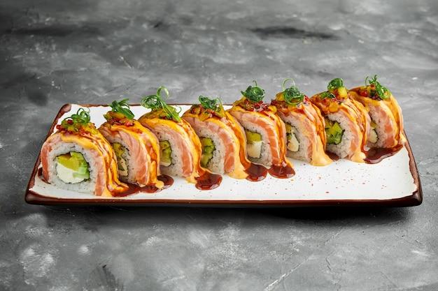 スモークサーモン、スクランブルエッグ、アボカド、クリームチーズにうなぎとスパイシーソースをトッピングした日本の巻き寿司。灰色のテーブルの上の白いプレートの寿司。コピースペース