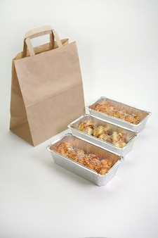 Japanese sushi rolls in foil containers on an isolated white wall. the concept of delivery