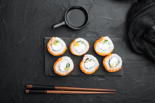 검은 돌 위에 와사비와 연어 생선 세트를 곁들인 구운 에비라는 이름의 일본 스시 롤