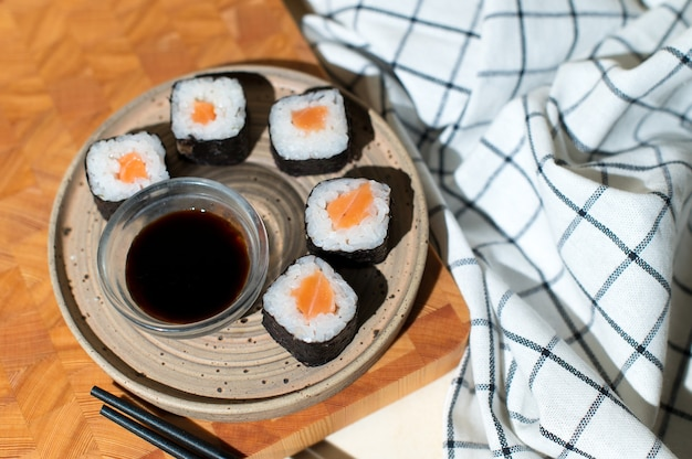 Japanese sushi rolls served on plate on wooden background