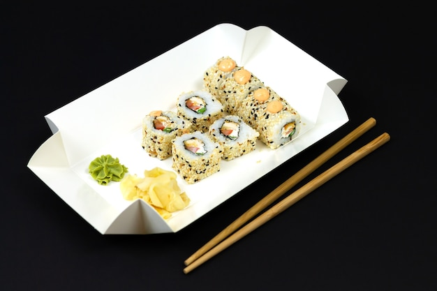 Japanese sushi rolls in white eco paper disposable box on dark background