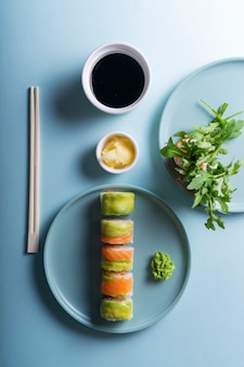 Japanese sushi rolls with avocado and salmon, in a modern minimalist style. on a blue background with hard shadows
