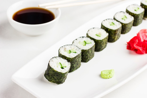Japanese sushi rolls with cucumber, serving with soy sauce, wasabi and ginger on white background