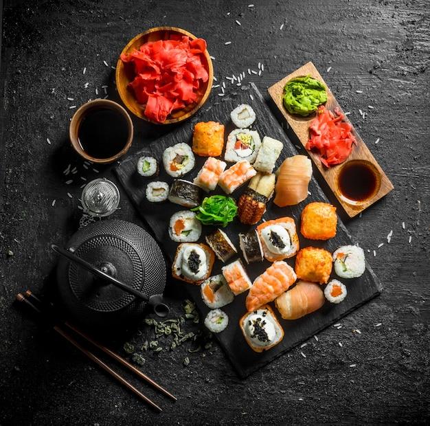 鮭、アボカド、エビの巻き寿司。黒い素朴なテーブルの上