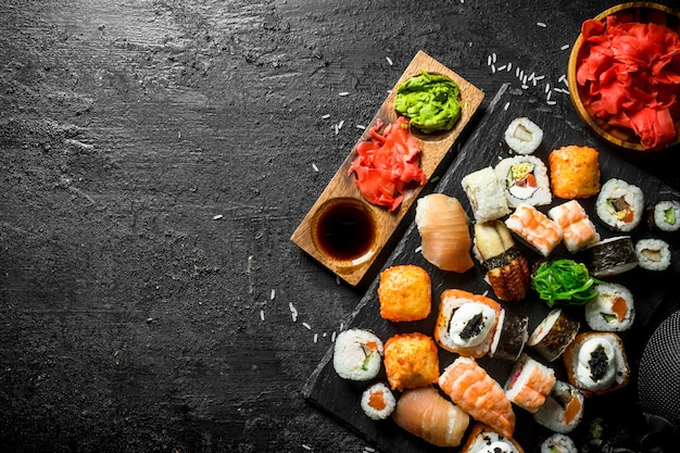 Japanese sushi rolls with salmon, avocado and shrimp. on black rustic background