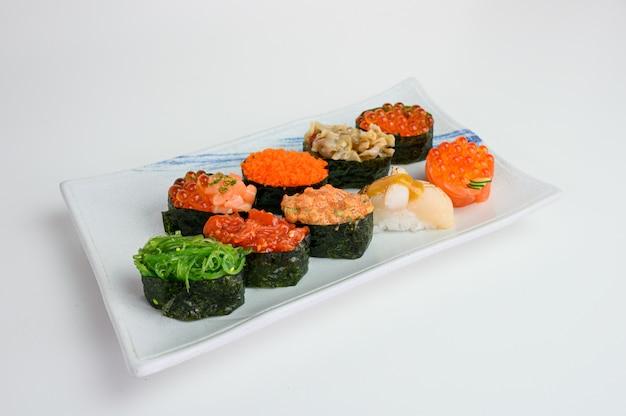 Japanese sushi of seaweed roll with ikura, ebiko, hotate, wakame, kurage on ceramic plate