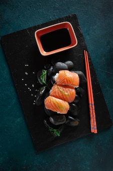 日本の寿司は黒い石の上で出されます。上面図、暗い背景にクローズアップ。