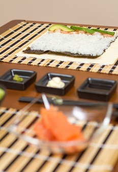 Japanese sushi with rice ready to roll on a table