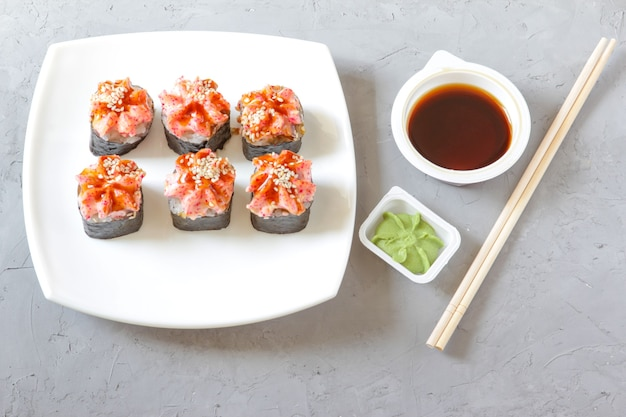 회색 콘크리트 배경 위에 젓가락을 얹은 간장과 와사비를 곁들인 일본 스시