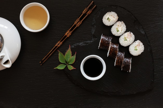 Japanese sushi with soy sauce on heart shape black  dish with chopsticks and traditional tea.