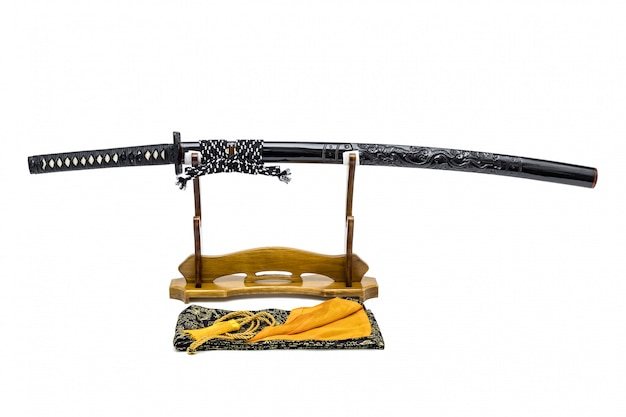 Japanese sword with shiny black dragon scabbard  on wooden stand and silk bag in the front