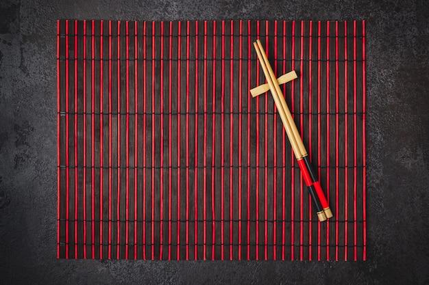 Японская сервировка стола. бамбуковые палочки для еды и коврик красно-черного цвета.