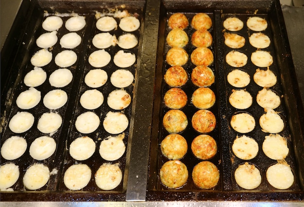 Japanese takoyaki octopus balls being grilled in the molded pan