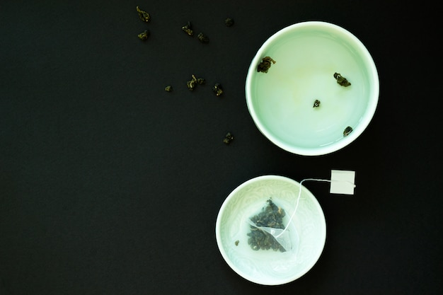 Japanese tea cup and saucer with a bag of tea leaves on black background. tea party.