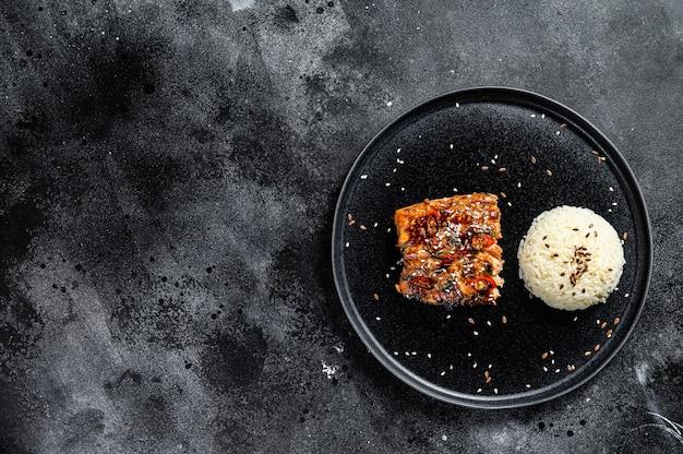Филе лосося на гриле по-японски терияки в восхитительном соусе с гарниром из риса. черный фон