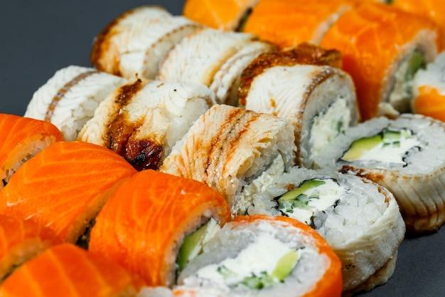 일본 전통 음식. 신선한 연어 아보카도와 크림 치즈, 간장을 곁들인 스시 롤 세트