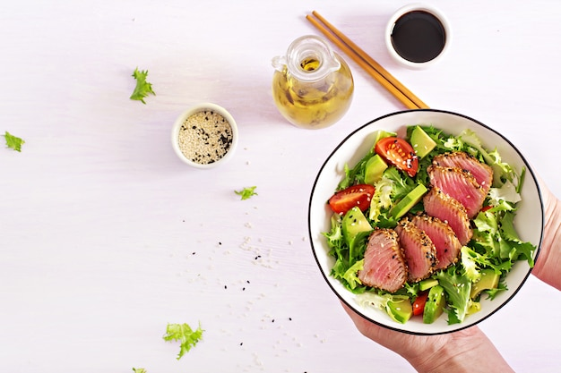 Japanese traditional salad with pieces of medium-rare grilled ahi tuna and sesame with fresh vegetable salad on a plate.