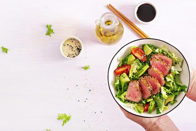 Японский традиционный салат с кусочками средне-редкого жареного тунца ахи и кунжута с салатом из свежих овощей на тарелке