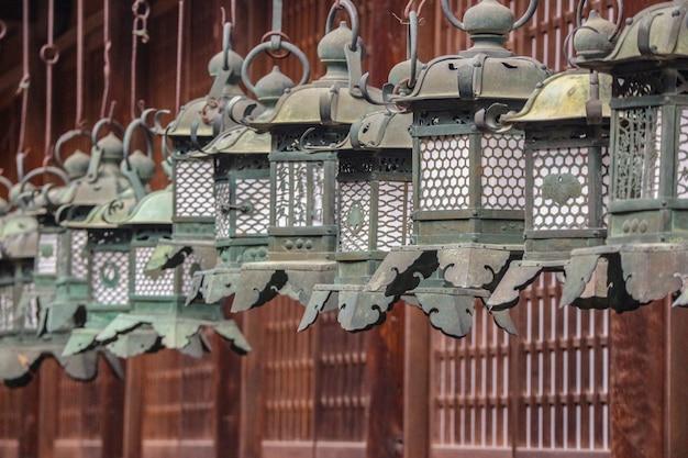 Japanese traditional steel lanterns hanging around kasuga shrine temple.
