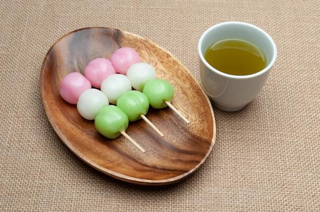 緑茶と木の大皿にだんご餅と呼ばれる日本の伝統的なお菓子