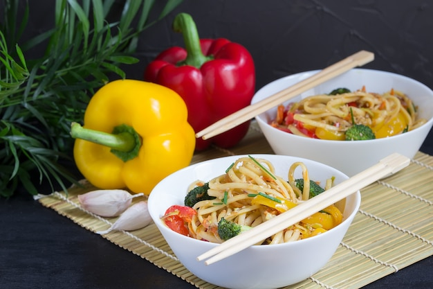 Japanese two bowls of stir fry noodles with vegetables, soy sauce and peppers on a bamboo mat