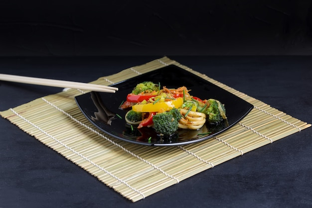 Japanese udon noodles on a black plate with vegetables and soy sauce on a bamboo mat