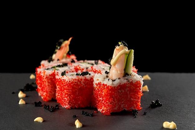 Japanese uramaki with shrimp, decorated with red roe.