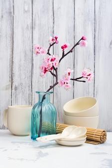 Japanese utensils, dinnerware, chopsticks and branch of blooming sakura on white