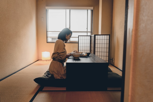 Japanese woman eating in a traditional apartment